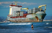 FREIGHTENED_Swimmers-share-the-beach-with-a-rusty-container-ship